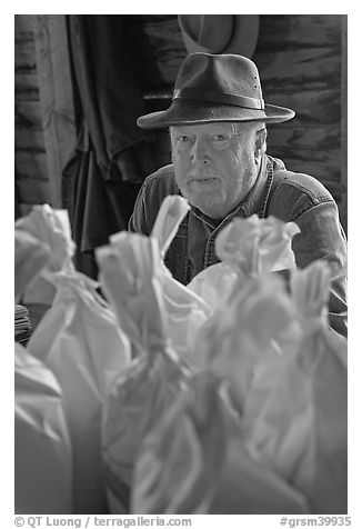 Miller sitting behind bags of cornmeal, North Carolina. Great Smoky Mountains National Park (black and white)