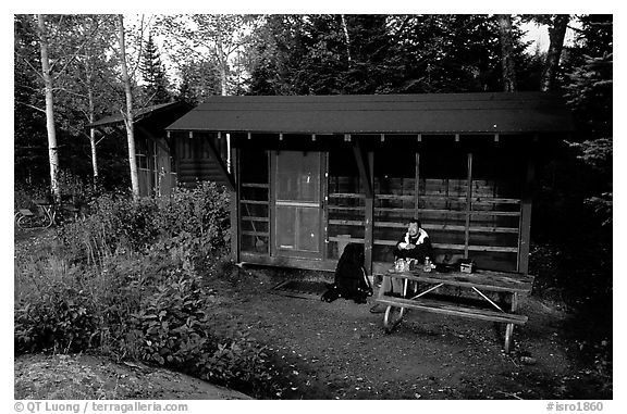 Backpacker sitting in shelter at Chippewa harbor. Isle Royale National Park (black and white)