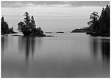 Tree-covered islet and smooth waters, Chippewa Harbor. Isle Royale National Park, Michigan, USA. (black and white)