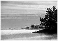 Fog lifting up in early morning and trees on shore of Kabetogama lake. Voyageurs National Park ( black and white)