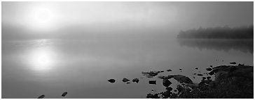Misty lake scene with sun piercing fog. Voyageurs National Park (Panoramic black and white)