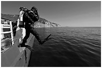 Scuba diver stepping out of boat, Santa Cruz Island. Channel Islands National Park, California, USA. (black and white)