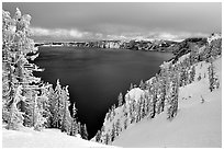 Trees and lake in winter with clouds and dark waters. Crater Lake National Park ( black and white)