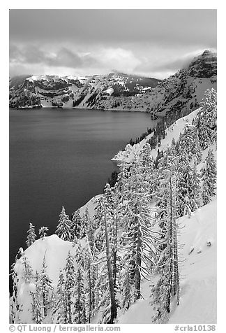 Cliffs, conifer trees, and lake in winter with cloudy skies. Crater Lake National Park (black and white)
