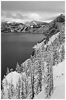 Cliffs, conifer trees, and lake in winter with cloudy skies. Crater Lake National Park, Oregon, USA. (black and white)