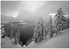 Snowy trees and lake with low clouds colored by sunset. Crater Lake National Park, Oregon, USA. (black and white)