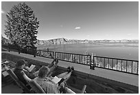 Reading on Crater Lake Lodge Terrace overlooking  Lake. Crater Lake National Park, Oregon, USA. (black and white)