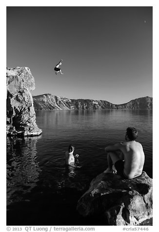 Man jumping from cliff as others look, Cleetwood Cove. Crater Lake National Park (black and white)