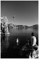 Man jumping from cliff as others look, Cleetwood Cove. Crater Lake National Park ( black and white)