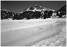 Turquoise melting snow in lake Helen and Lassen Peak, late spring. Lassen Volcanic National Park, California, USA. (black and white)