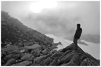 Hiker on ridge waches foggy sunset, North Cascades National Park.  ( black and white)