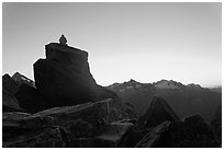 Man sitting on rock contemplates mountains at sunrise, North Cascades National Park.  ( black and white)