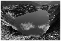 Fluffy clouds reflected in blue lake, North Cascades National Park.  ( black and white)
