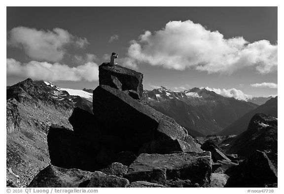 Man sitting on rock photographs mountain panorama, North Cascades National Park.  (black and white)