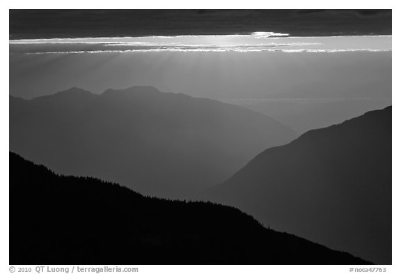 Layered ridges with sun behind clouds, North Cascades National Park.  (black and white)
