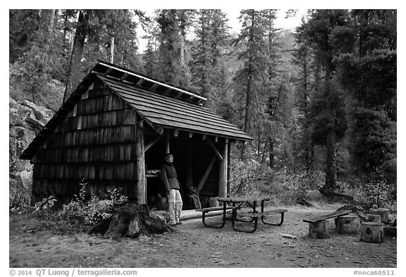 Hiker at high Bridge campground shelter, North Cascades National Park.  (black and white)