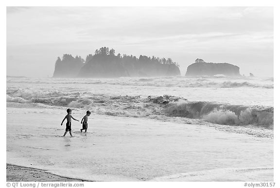 Children playing in water in front of sea stacks, Rialto Beach. Olympic National Park (black and white)
