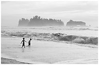 Children playing in water in front of sea stacks, Rialto Beach. Olympic National Park, Washington, USA. (black and white)