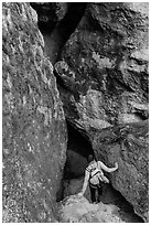 Woman walking into Balconies Cave. Pinnacles National Park, California, USA. (black and white)