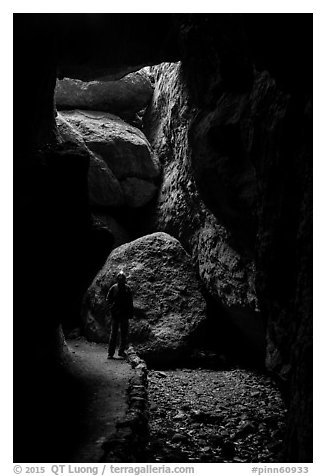 Hiker with headlamp in Bear Gulch Cave. Pinnacles National Park (black and white)