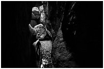 Hiker with lamp in Bear Gulch Cave. Pinnacles National Park ( black and white)
