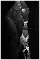 Hiker in narrow and deep section of Lower Bear Gulch Cave. Pinnacles National Park ( black and white)