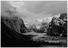 View with fog in valley and peaks lighted by sunset, winter. Yosemite National Park, California, USA. (black and white)