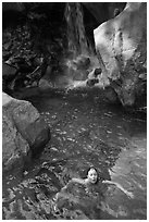 Girl swims in cool pool at the base of Wapama falls. Yosemite National Park, California, USA. (black and white)