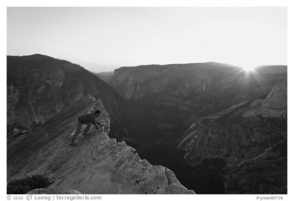 Hiker looking over the edge of the Diving Board, sunset. Yosemite National Park (black and white)