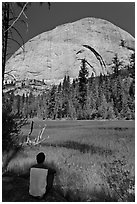 Hiker sitting at Lost Lake on west side Half-Dome. Yosemite National Park, California, USA. (black and white)