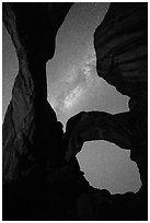 Milky Way appearing above Double Arch. Arches National Park, Utah, USA. (black and white)