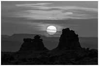 Sun setting between rock towers. Arches National Park, Utah, USA. (black and white)