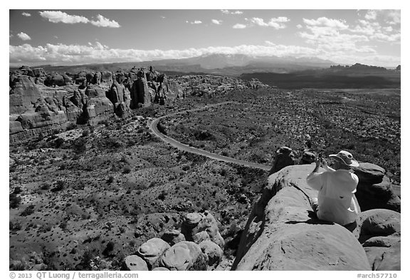 Tourist taking picture from top of fin. Arches National Park (black and white)