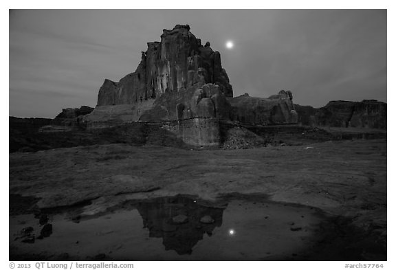 Courthouse tower and moon reflected in pothole. Arches National Park (black and white)