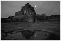 Courthouse tower and moon reflected in pothole. Arches National Park, Utah, USA. (black and white)