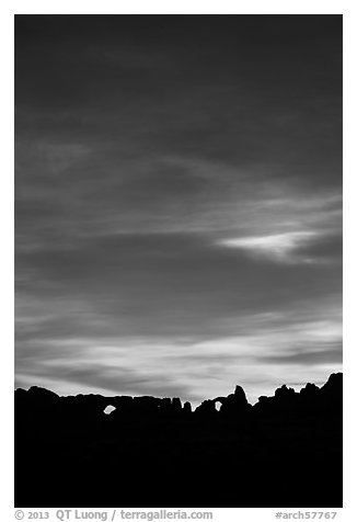 Windows and Turret Arch silhouetted against colorful clouds. Arches National Park (black and white)