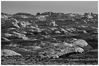 Sandstone domes with arch in background. Arches National Park, Utah, USA. (black and white)