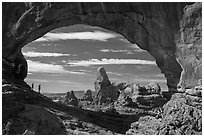 Family in the North Window span. Arches National Park, Utah, USA. (black and white)