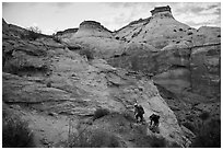 Hikers climbing out of High Spur slot canyon, Orange Cliffs Unit, Glen Canyon National Recreation Area, Utah. USA ( black and white)