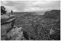 Park visitor looking, Wingate Cliffs at Flint Trail overlook. Canyonlands National Park, Utah, USA. (black and white)