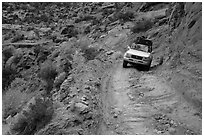 High clearance four-wheel-drive vehicle on the Flint Trail,  Orange Cliffs Unit,  Glen Canyon National Recreation Area, Utah. USA (black and white)
