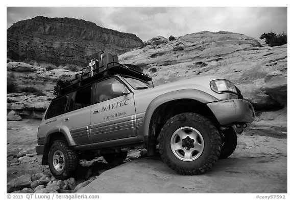 Expedition vehicle driving over rock ledge, Teapot Canyon. Canyonlands National Park (black and white)