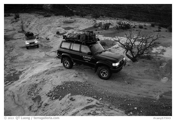 4WD vehicles driving over rock at dusk in Teapot Canyon. Canyonlands National Park (black and white)