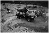 4WD vehicles driving over rock at dusk in Teapot Canyon. Canyonlands National Park, Utah, USA. (black and white)