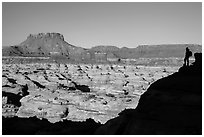 Hiker silhouette above the Maze and Chocolate drops. Canyonlands National Park, Utah, USA. (black and white)