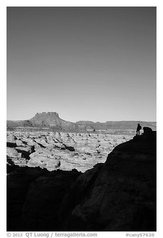 Hiker standing in silhouette above the Maze. Canyonlands National Park (black and white)