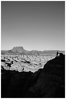 Hiker standing in silhouette above the Maze. Canyonlands National Park, Utah, USA. (black and white)