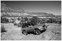 4WD vehicle driving over rocks in Teapot Canyon. Canyonlands National Park, Utah, USA. (black and white)