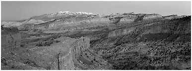 Panorama of multi-hued cliffs and Henry Mountains at dusk. Capitol Reef National Park (Panoramic black and white)