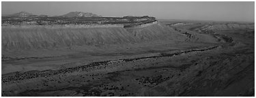 Long chain of cliffs of the Waterpocket Fold at dusk. Capitol Reef National Park (Panoramic black and white)